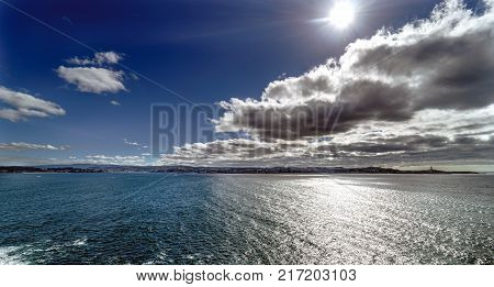 Panoramic view of the city of La Coruna and its bay on the coast of Galicia (Spain). Sky with clouds with reflections and sun facing