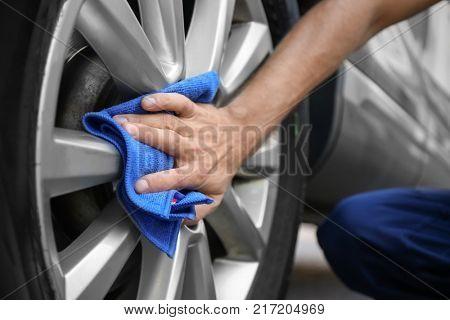 Man washing automobile wheel with rag outdoors