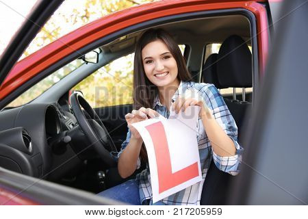 Happy young woman tearing learner driver sign in car