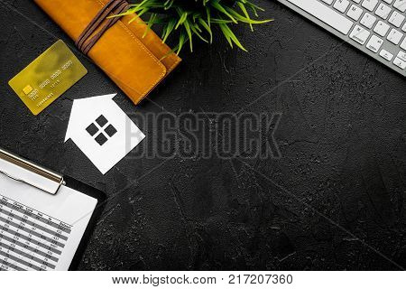 Mortgage payment schedule near bank card and wallet on black background top view.