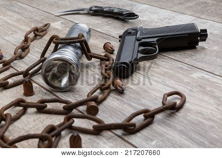 A rusty chain with a gun, a silver flashlight, bullets and a folding knife lie on a wooden background