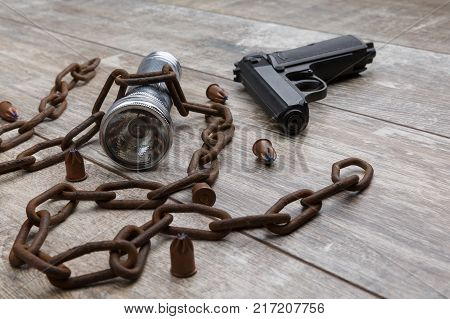 A rusty chain with a gun, a silver flashlight, bullets close-up lie on a wooden background