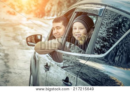 Happiness caucasian smilling boy with his father looking out of black car window in sunny day at winter time near the forest.