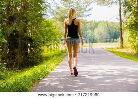 Young woman walks alone on a trail in the woods and listens to music.