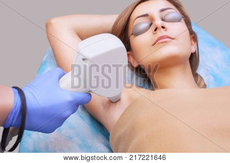 The cosmetologist does the laser hair removal procedure in the armpit zone to a young woman in a beauty salon.