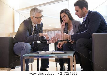 Real-estate agent explaining financial plan to couple buying new home