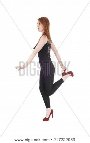 A beautiful brunette woman in a black outfit and high heels standing on one leg looking serious isolated for white background
