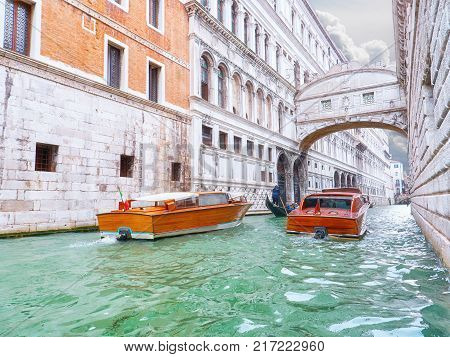 Traditional boats taxi passing over Bridge of Sighs in Venice, Italy