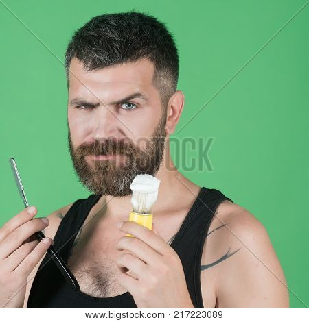 Haircut of bearded man archaism. Barber and hairdresser. Fashion and beauty innovation. Man cut beard and mustache with razor and shaving brush. Serious hipster in barbershop new technology