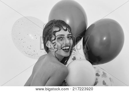 Happy pretty girl or sexy woman with cute curly lock blond hair fashion hairstyle and rosy lips stylish makeup on young face smiling with party balloons pink hearts on white background