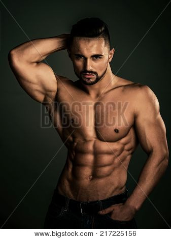 Dieting and fitness. Athletic bodybuilder man on black background. Man with muscular body and torso. Sport and workout. Coach sportsman with bare chest in jeans.