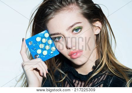 Dieting pill and vitamin at girl. Woman with pills in blister pack. Health and medicine. Drug and antidepressant. Treatment and hypnotic tablet.