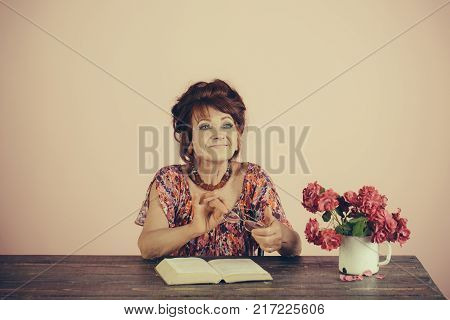 Pension and retirement old age. happy old lady or grandmother. Writer and poet granny read fairytale. Teacher or professor education teachers day. Old woman reading book with glasses at flowers.