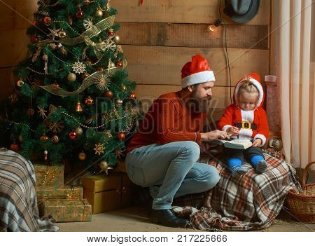 Winter holiday and vacation. Xmas party celebration fathers day. New year small boy and man fairytale. Christmas happy child and father read book. Santa claus kid and bearded man at Christmas tree.
