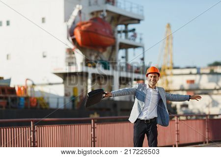 Successful Business Man In Gray Suit And Protective Construction Orange Helmet With Tablet On Backgr
