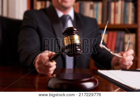 Male lawyer or judge hand's striking the gavel on sounding block, working with Law books and document, report the case on table in law office, tribunal and justice concept, close-up