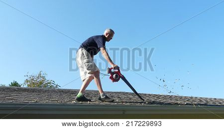 A homeowner is on the roof of his residence using a leaf blower to remove leaves from the gutter in preparation for storm season water runoff.