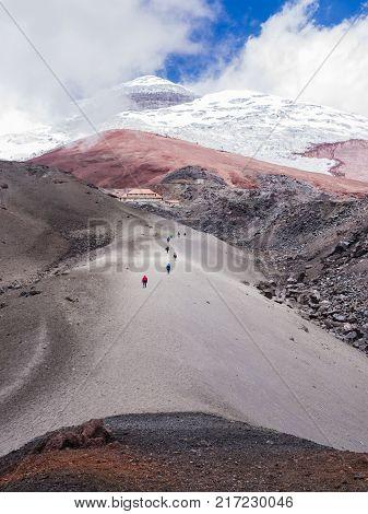 Backpackers climbing Cotopaxi volcano along a pyroclastic rocks hiking trail, Ecuador