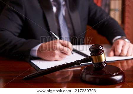 Male Judge with law gavel or judge mallet sitting and working in courtroom, close-up portrait. Justice and law concept
