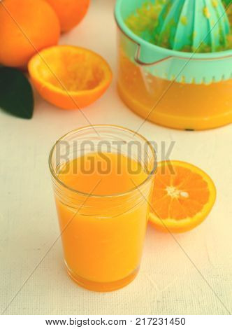 Freshly squeezed orange juice in glass on white background, vertical, toned