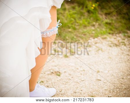 the bride with sneakers and his garter belt walks on the stony path