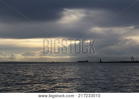 The rays of the sun make their way through thunderclouds in the harbor in the autumn evening.