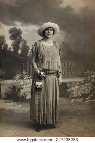 Lady in hat. Authentic antique black and white photograph from old family album. 1920s.