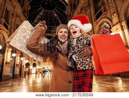 Fun Christmas family trip to Milan Italy. smiling young mother and child travellers in the front of Duomo in Milan Italy hugging