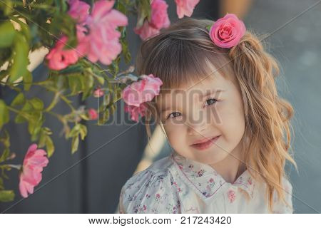 Cute baby girl with blond curly hairs and happy bright child eyes posing in central park close to huge bush of flowers red white pink roses wearing summer stylish clothes.