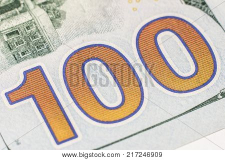 A super close-up of the number 100 on a hundred-dollar bill of the United States.