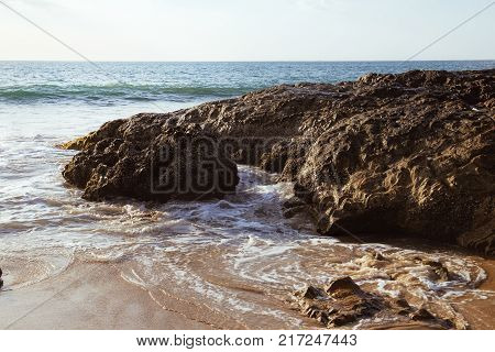 Beautiful seascape with sea and rock in Nang Thong Beach, Khao Lak, Thailand. View of sea waves with protruding stones and whirlpools. Nature composition.