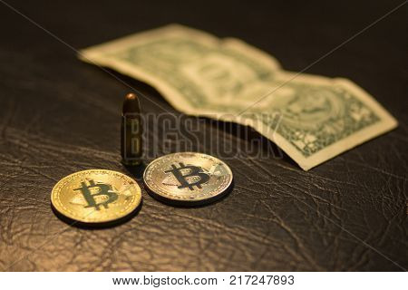 A close-up of a pistol cartridge with a bullet, a silver and gold bitcoin and one US dollar on a black leather background. Toned.