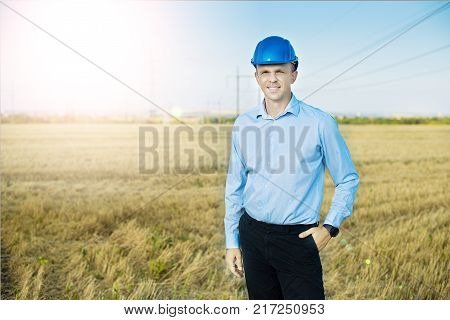 Young blue collar worker or engineer wearing in yellow helmet stands in the field with wide smile. Half-length portrait.