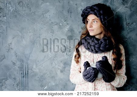 Winter fashion accessories.Young woman dressed for cold weather in grey snood hat and mittens holding a cup of tea.