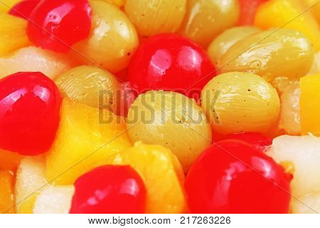 Fruit salad texture. Fruits as background pattern. Exotic Fruits Fruit salad with cocktail cherry sour cherry mango pineapple grapes, pear, maracuja, papaya in syrup. Food.
