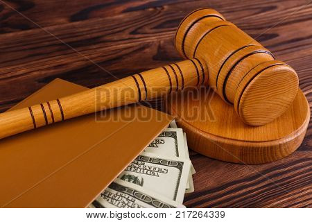 A wooden auctioneer's hammer on a round stand, a brown notepad in which there are a lot of dollar bills. Close-up.