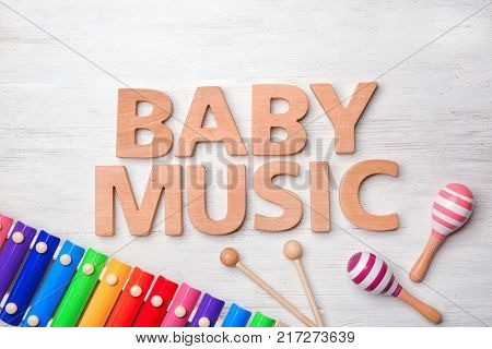 Text BABY MUSIC and toys on wooden background