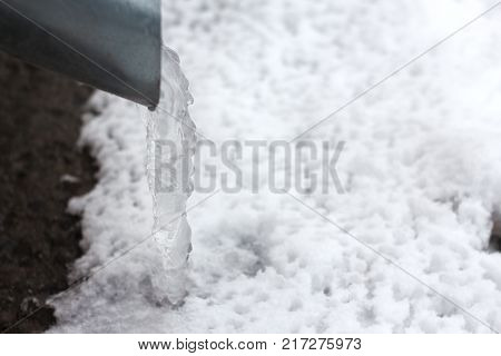 frozen water in a drainpipe, with hanging icicles . poster