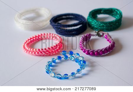 Five Bracelets Lie On A Light Background.
