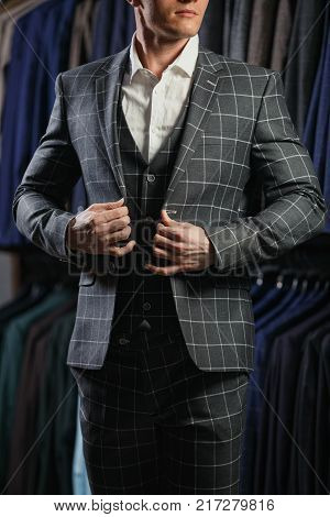 Handsome fashion model in a suit, against row of suits in shop