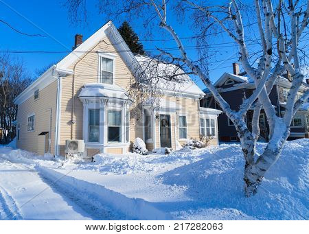 Older traditional house in wintertime in a North American neighborhood.