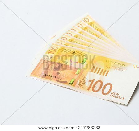 Several banknotes of a new type with a portrait of poet Lea Goldberg worth 100 Israeli shekels isolated on a white background