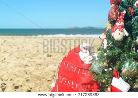 Christmas at the beach, red Santa bag of presents, stockings and decorated tree in the sand on sunny day.