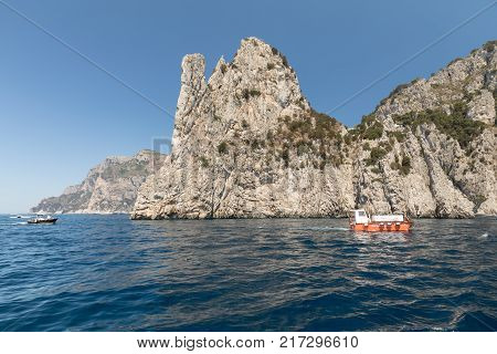 CAPRI ITALY - JUNE 13 2017: View from the boat on the Boats with tourists and the cliff coast of Capri Island Italy