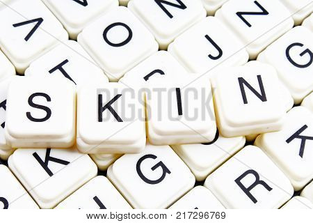 poster of Skin title text word crossword. Alphabet letter blocks game texture background. White alphabetical letters on black background.