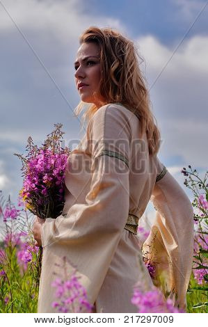Beautiful sad woman in traditional dress relaxes with bunch of flowers on fireweed meadow