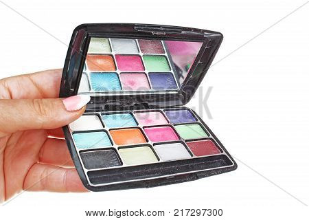 Woman hand holding cosmetic eyeshadow makeup palette on isolated white cutout background. Studio photo with studio lighting easy to use for every concept. Colorful eyeshadows.