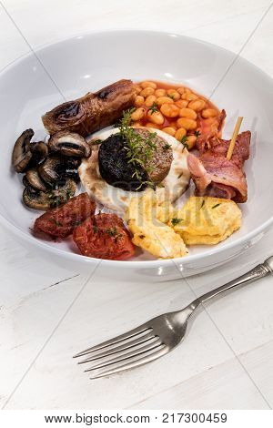 irish breakfast with thyme served on a white plate
