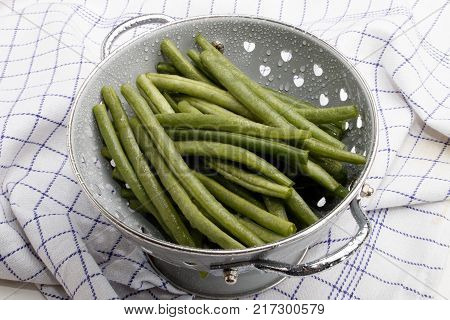 organic wet green beans and water drops in a colander
