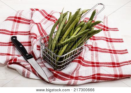 organic green beans in a metal basket and a knife to cut